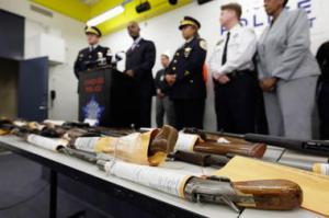 Chicago police officials speak at a news conference Monday with a display of recently seized guns, part of the 574 that had been seized in the city since Jan. 1. The city suffered through its deadliest January in more than a decade. M. Spencer Green/AP In Pictures American Gun Culture