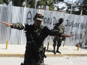www.businessinsider.com A military police officer gestures while stopping a vehicle at a checkpoint in the neighbourhood of Flor del Campo in Tegucigalpa October 14, 2013. Read more: http://www.businessinsider.com/the-most-violent-cities-in-the-world-2013-11?op=1#ixzz2mHvMMsTI